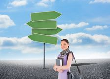 Attractive student holding books and her bag while standing Royalty Free Stock Images