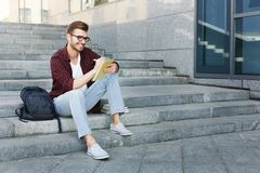 Attractive student making notes sitting on stairs outdoors. Attractive student sitting on stairs outdoors making notes, preparing for exams at the university or Stock Images