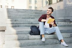 Student sitting on the stairs, writing notes and dreaming outdoors. Attractive student sitting on the stairs, writing notes to his notebook, preparing for exams Royalty Free Stock Photo
