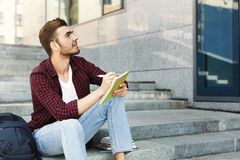 Student sitting on the stairs, writing notes and dreaming outdoors. Attractive student sitting on the stairs, writing notes to his notebook, preparing for exams Royalty Free Stock Image