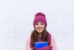 Attractive Student Smile Teenage Girl In Pink Hat Holding Folder Pencil. Over White Brick Background Stock Photography