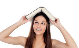 Attractive student woman with brackets an a book on the head Royalty Free Stock Photography
