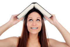 Attractive student woman with brackets an a book on the head Stock Photos
