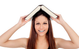 Attractive student woman with brackets an a book on the head Stock Images