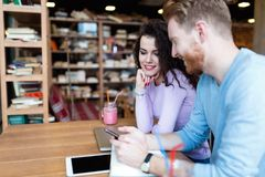 Attractive students learning together in coffee shop Stock Image