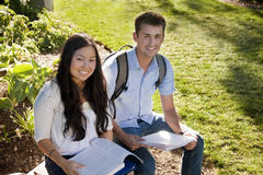Attractive Students studying. Young, attractive male and female students outside studying Royalty Free Stock Image