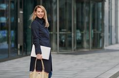 Attractive stylish blond businesswoman walking through town. Pausing to look back at the camera with a warm friendly smile in front of an office block entrance royalty free stock images