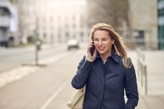 Attractive stylish blond woman chatting on her smartphone. As she walks down a quiet high key urban street smiling as she listens to the conversation with copy royalty free stock photos