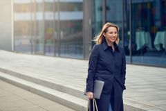 Attractive stylish blond woman leaving her workplace. As she walks down a quiet high key urban street smiling as she carries her laptop with copy space royalty free stock images