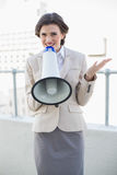 Attractive stylish brown haired businesswoman speaking in a megaphone Royalty Free Stock Photos