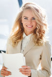 Attractive stylish businesswoman in beige jacket, holding paper in hand Stock Photography