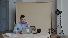 Attractive stylish creative worker or photographer talking on the smartphone and sitting in modern daylight workplace stock video