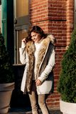 Attractive stylish girl dressed in a white knitted sweater, light pants and a light coat with fur poses in the street stock photography