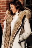 Attractive stylish girl dressed in a white knitted sweater, light pants and a light coat with fur poses in the street royalty free stock photography