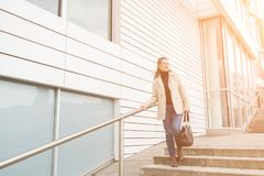 Attractive stylish mature woman descending steps. Attractive stylish mature woman descending exterior steps in town by the warm glow of the sun looking off to Stock Photos