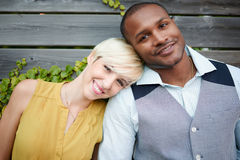Attractive and stylish multicultural couple in love cuddling by a fence in an ivy-filled urban setting Stock Photos
