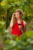 Attractive stylish woman drinking glass of red wine in vineyard Stock Photography