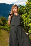 Attractive stylish woman drinking glass of red wine in vineyard Royalty Free Stock Images