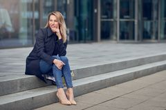 Attractive stylish woman in high heels and an overcoat. Sitting on urban steps looking thoughtfully to the side with her chin on her hand stock photo
