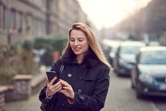 Attractive stylish woman with long blond hair using her mobile. In an urban street in a busy town smiling as she reads a text message stock image