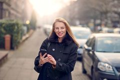 Attractive stylish woman with long blond hair using her mobile. In an urban street in a busy town smiling as she reads a text message stock photos