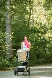 Attractive stylish woman pushing a baby stroller along a rural r Stock Image