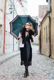 Attractive, stylish woman walking with an umbrella Stock Photo