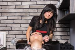 Attractive stylist wiping off the remains of paint with a cotton. Disc from the head of women after washing her hair in washing sink in beauty salon Stock Photos