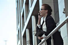 Attractive success business woman smiling and talking on smartphone. Royalty Free Stock Photos