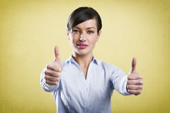 Attractive successful businesswoman giving thumbs up. Stock Photo