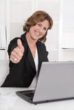Attractive successful smiling secretary with thumb at desk. Royalty Free Stock Photo