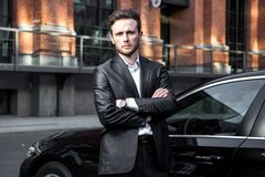 Attractive successful young businessman in a business suit near his premium class car. Attractive successful young businessman in a business suit near his car royalty free stock image