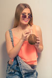 Attractive summer girl. Attractive girl in summer clothes and sun glasses is drinking a coconut milk, looking at camera and smiling, against gray background Stock Photo