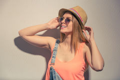 Attractive summer girl. Attractive girl in summer clothes and sun glasses is holding hat, looking away and smiling, against gray background Royalty Free Stock Photo