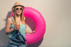 Attractive summer girl. Attractive girl in summer clothes and sun glasses is holding a swim ring and a glass of juice, looking at camera and smiling, against Stock Photos