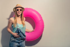 Attractive summer girl. Attractive girl in summer clothes and sun glasses is holding a swim ring, looking at camera and smiling, against gray background Royalty Free Stock Photography