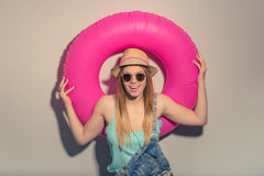 Attractive summer girl. Attractive girl in summer clothes and sun glasses is holding a swim ring, looking at camera and smiling, against gray background Royalty Free Stock Images