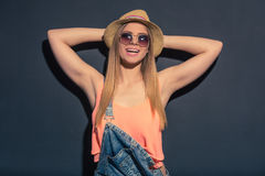 Attractive summer girl. Portrait of attractive girl in summer clothes and sun glasses looking at camera and smiling, standing with hands behind head against dark Royalty Free Stock Photography