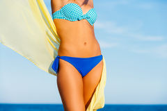 Attractive suntanned female body. Close up front view of Attractive suntanned female body on beach against blue sky. Young woman in blue bikini holding yellow Royalty Free Stock Photos
