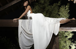 Attractive suntanned girl in white dress poses. Stock Photography