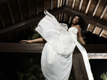 Attractive suntanned girl in white dress poses. Royalty Free Stock Photo