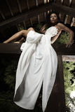 Attractive suntanned girl in white dress poses. Royalty Free Stock Images