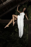 Attractive suntanned girl in white dress poses. Attractive suntanned girl in white dress poses on a wooden beam Royalty Free Stock Image