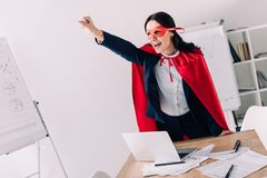 attractive super businesswoman in cape and mask screaming and standing with hand up royalty free stock photos