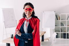 attractive super businesswoman in cape and mask standing with crossed arms royalty free stock images