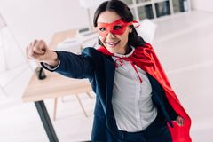 Attractive super businesswoman in cape and mask standing with hand up. In office stock images