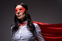 Attractive super businesswoman in red cape and mask. On black royalty free stock image
