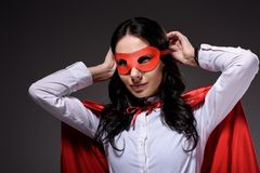attractive super businesswoman in red cape tying mask stock photo