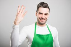 Attractive supermarket employer showing number four. And smiling on white background Stock Photos