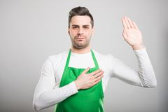 Attractive supermarket employer taking oath. Looking serious on white background Royalty Free Stock Photography
